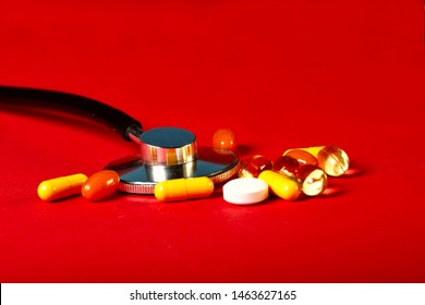 A group of bright medicine pills and a phonendoscope on a red background. Cropped shot, horizontal, side view. The concept of medicine and health. Crisis opioid painkiller and drug addiction concept.