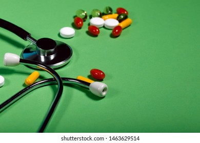 A group of bright medicine pills and a phonendoscope on a green background. Cropped shot, horizontal, side view. The concept of medicine and health. Crisis opioid painkiller and drug addiction concept