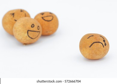 A group of brown ball laughing in the background while the brown ball in front alone and look sad and depressed. Concept of discrimination,bully,mental illness.