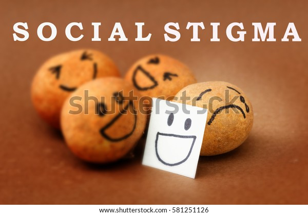 A group of brown ball laughing but one is crying while hiding the feeling with a smiling mask. Concept of social stigma which lead to people with problems hiding the problems or refuse help.