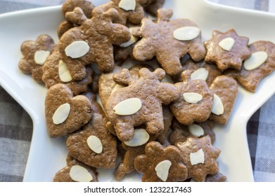 Group of brown moravian dark gingerbreads with sliced almonds, christmas cookies, reindeer shapes on white star shape plate, one by one
