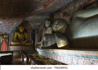 Group of Buddha statues in cave buddhist temple with bright painted murals on walls and ceiling