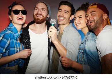 Group of buddies singing karaoke in club