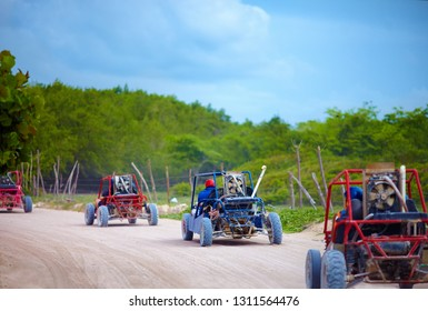 group of buggy vehicles riding on dusty countryside road during extrim tourist trip