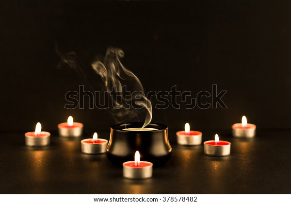 Group of burning candles and a big candle extinguished in the middle with intricate smoke patter rising.