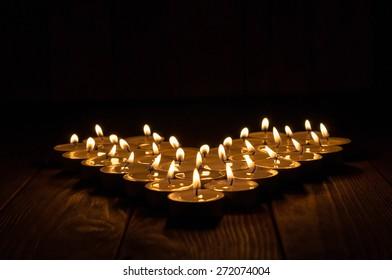 Group of burning candles on  black background.