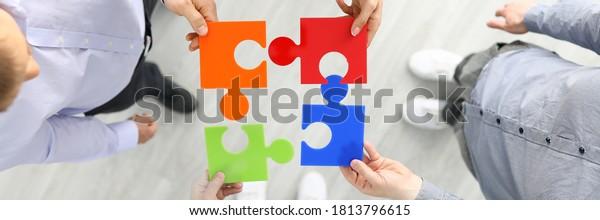 Gruppenmitarbeiter halten ein Rätsel für Farbelemente, der den Hintergrund für die Draufsicht, Nahaufnahme, enthält. Jeder erfüllt seine Aufgabenverteilung des Arbeitskonzepts