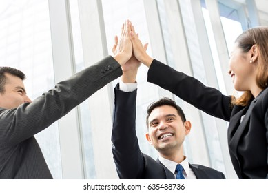 Group of business colleagues giving high five celebrating success