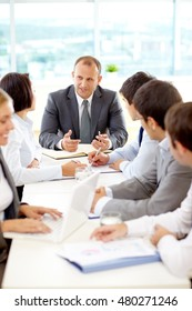 Group of business colleagues listening to a businessman during a meeting in a conference room