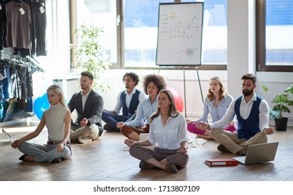 group of business colleagues meditating at work, sitting on the floor. modern, business, meditation concept