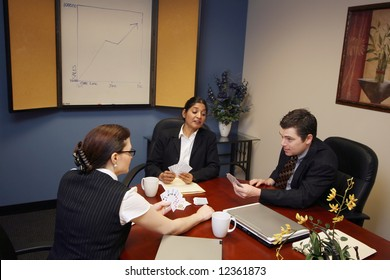 Group of business colleagues sitting in a conference room and playing cards instead of working