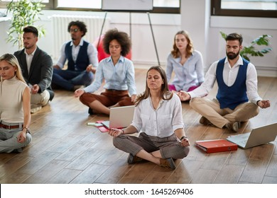group of business coworkers meditating at work, sitting on the floor. modern, business, meditation