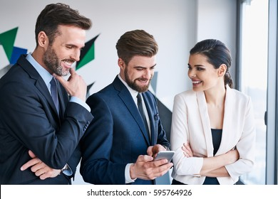 Group of business executives talking during coffee break at office sharing something on smartphone