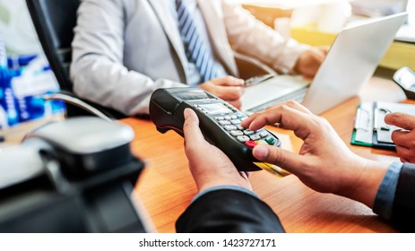 Group of business holding credit card with NFC payment system in modern office, asian people.