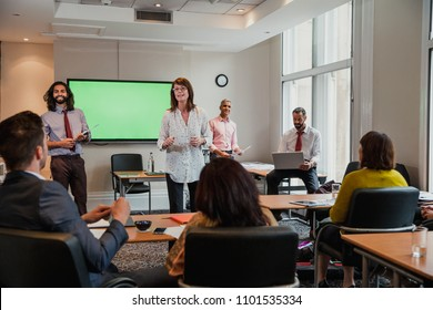 Group of business men and women giving a presentation to another small group of business men and women.