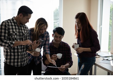 A group of business men and women talking to each other. Have a cup of coffee in hand. coffee break concept