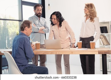 Group of business partners gathered at table with laptop and disposable coffee cups in office