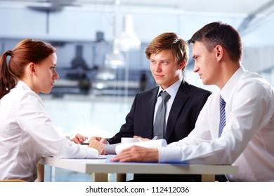 Group of business partners interacting at meeting with focus on young man