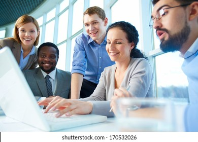 Group of business partners looking astonishingly at laptop display at meeting