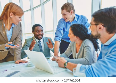 Group of business partners looking at smiling man at meeting
