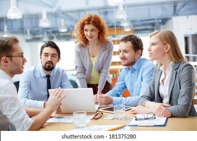 Group of business partners looking at young man presenting computer project at meeting