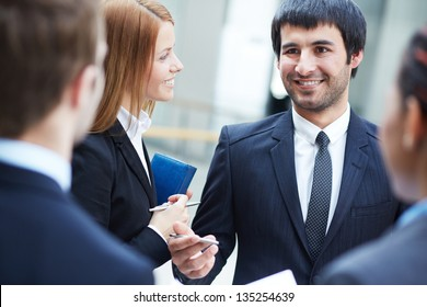 Group of business partners negotiating at meeting, focus on smart man