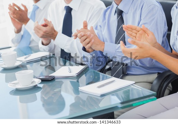 Group of business people applauding in the boardroom during a meeting