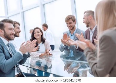 group of business people applauding sitting at the negotiating table