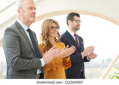 Group of business people applauding while celebrating successfull business.