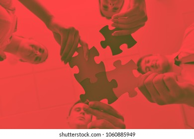Group of business people assembling jigsaw puzzle and represent team support and help conceptduo tone
