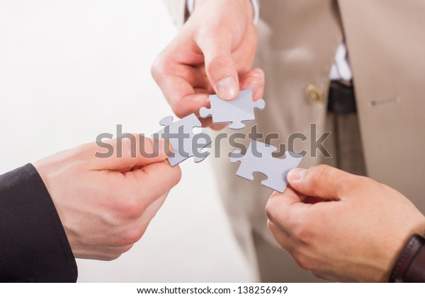 Group of business people assembling jigsaw puzzle. Teamwork. On white background.