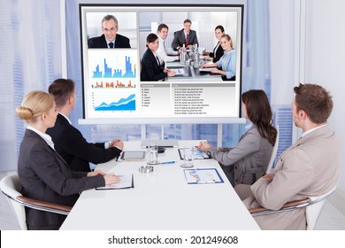 Group of business people attending video conference at table in office