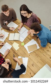 Group of business people in a brainstorming session seated around an office table discussing paperwork and ideas in a high angle view