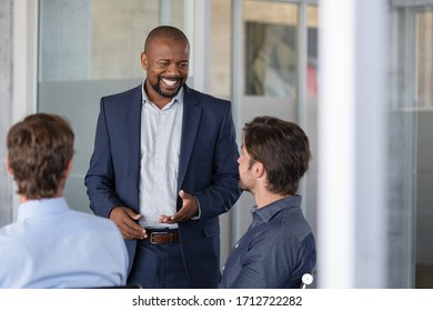 Group of business people brainstorming together in meeting room. Business colleagues discussing a new business strategy plan. Successful african american businessman doing presentation to his partners
