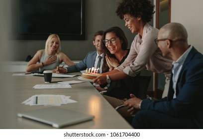 Group of business people celebrating a female executive's birthday in conference room. Team celebrating colleague's birthday in office during a meeting.