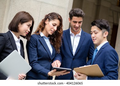 Group of business people chat outside of office