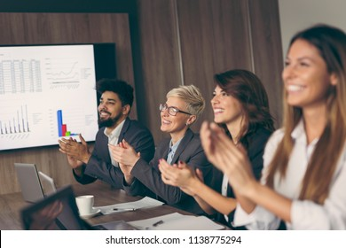 Group of business people in a conference room applauding after a successful presentation. Focus on the woman on the left