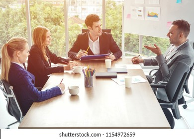 Group of business people discussing business in a meeting room with one empty chair.