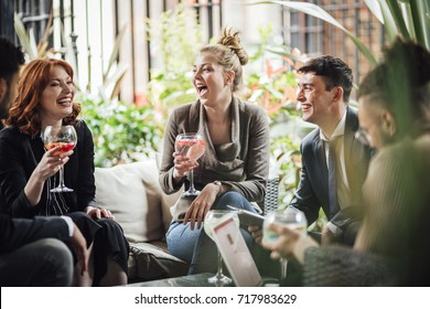 Group of business people are discussing their work in a bar courtyard after work. They are drinking cocktails and using technology.