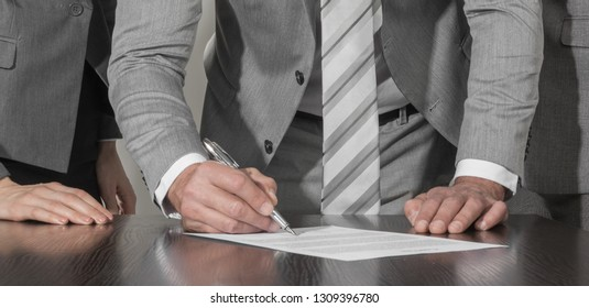 Group of business people in elegant suits standing at desk working in team together, working with documents sign up contract