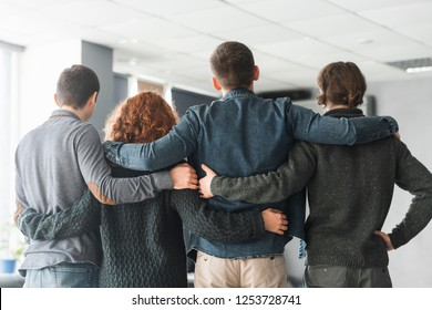 Group of business people embracing from behind