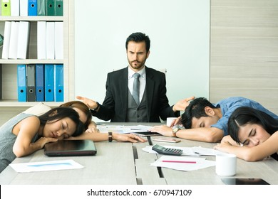 Group of business people exhausted from hard work and overworking so they falling asleep on the table while their boss shrugging shoulders to make don't know gesture during meeting in conference room