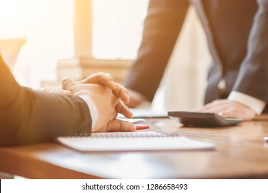 A group of business people gathered together in a meeting room to discuss business plans and market analysis before doing business. The consultant is analyzing and advising before investing.