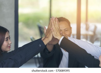 Group of Business People Giving High Five to Celebrate their Completion during a meeting, Business Team Making a Business Success, Feeling Happy. Business Teamwork Concept.
