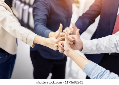 Group of Business people giving thumbs up gesture of approval an success, huddle together, showing unity and teamwork at office.