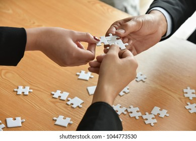 Group of Business people hands are holding and conecting jigsaw puzzle on desk and solving puzzle together at meeting in the office. Assembling, Solutions, Success and Strategy concept.
