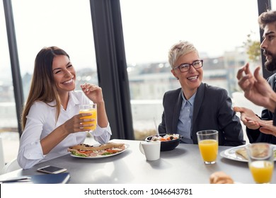 Group of business people having breakfast in company's restaurant. Focus on the woman on the left