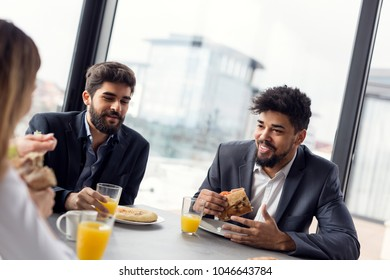 Group of business people having breakfast in company's restaurant. Focus on the man on the right