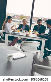 Group of business people having breakfast in company's restaurant.