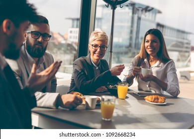 Group of business people having breakfast in company's restaurant. Focus on the women